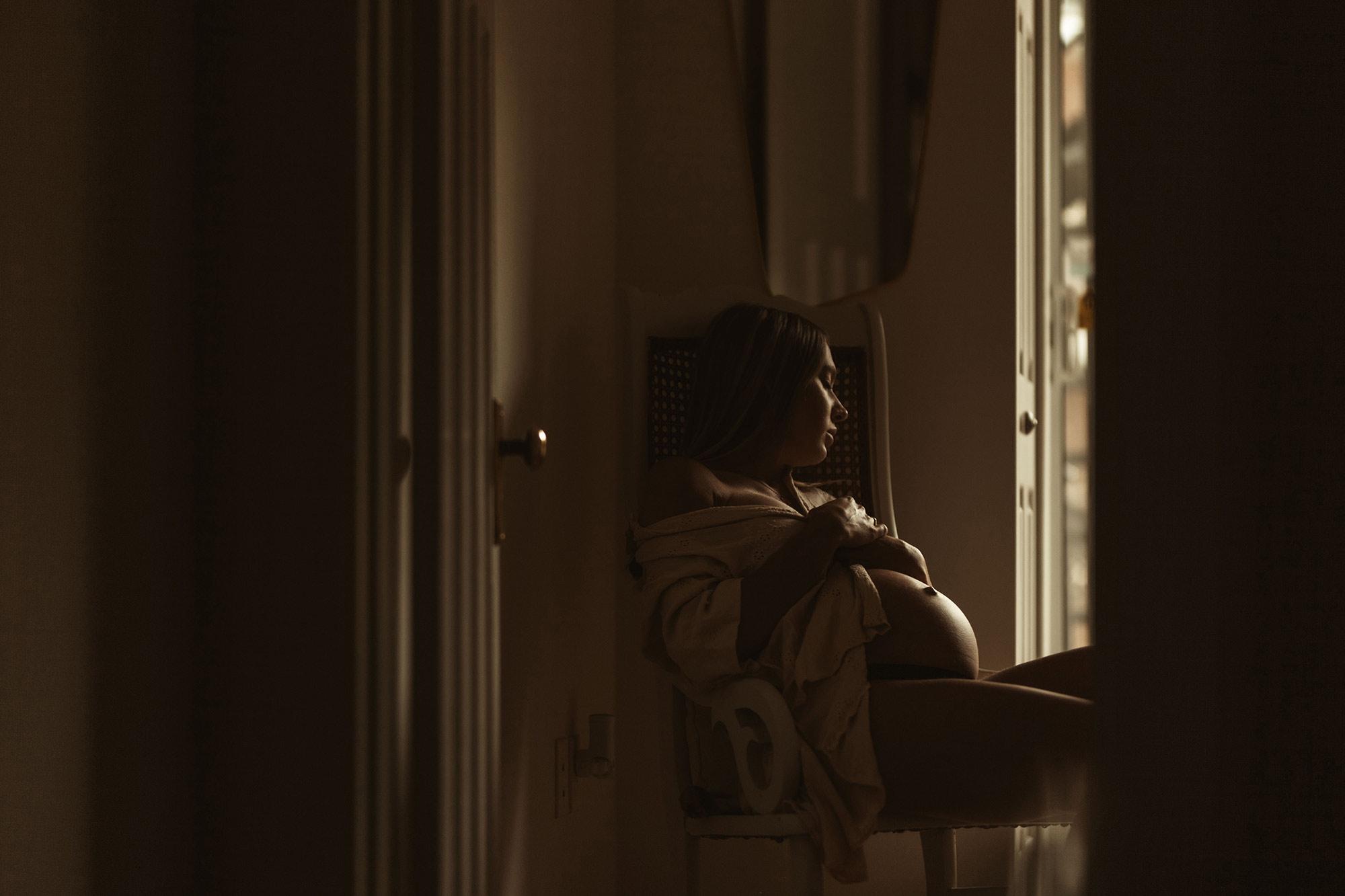 une femme enceinte assise sur une chaise avec les mains sur son ventre
